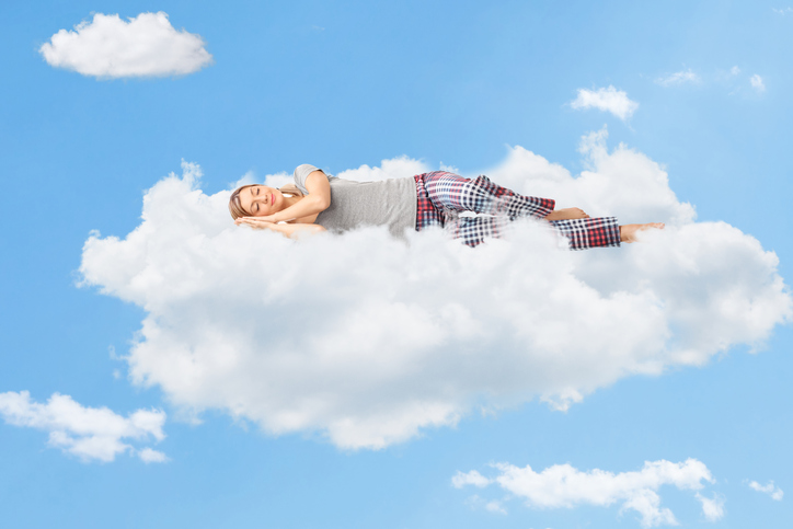 A woman having a great night's sleep symbolized by her sleeping on a cloud after receiving Sleep Apnea Treatment in Spokane Valley Washington.